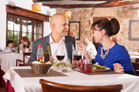 Photo pour Portrait of glad couple having romantic dinner in restaurant - image libre de droit