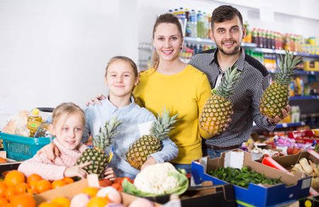 Cheerful family buyers during family shopping in vegetable department of grocery store