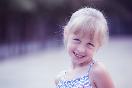 Closeup happy little girl posing on green city landscape