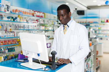 Photo for Experienced African American male pharmacist working on pc in modern pharmacy - Royalty Free Image