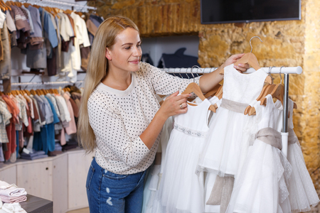 Young blonde woman choosing holiday dress for her little daughter in shop