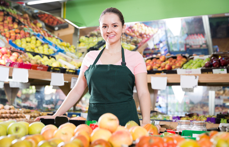 Portrait of young confident vendor of vegetable store standing behind counter