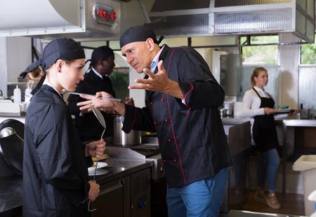 Foto de Exasperated head chef scolding upset female employee in kitchen of restaurant - Imagen libre de derechos