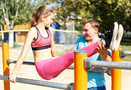 Foto de Father helping his sporty tweenager daughter do l-sit on parallel bars during workout on summer sports ground - Imagen libre de derechos