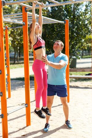 Foto de Smiling athletic man and tweenager girl exercising together on horizontal bar on summer sports ground - Imagen libre de derechos