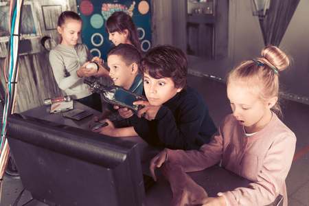 Photo pour Group of smiling children are concentrating on finding a way out of bunker quest room - image libre de droit