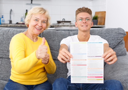 Photo for Happy senior mother and her adult son reading brochure with event announcements on sofa at kitchen - Royalty Free Image