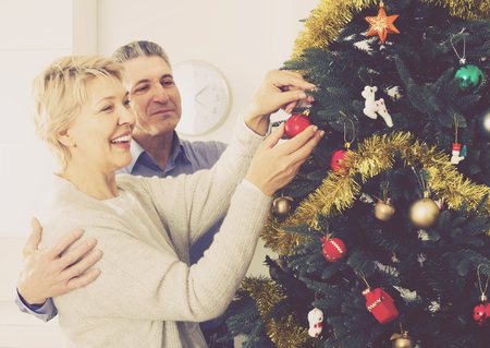 Mature smiling couple decorate fir-tree for holidays of Christmas and New Year at home