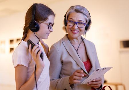 Foto de Senior female tutor and tweenage girl exploring art pieces in museum and listening commentaries in headphones - Imagen libre de derechos