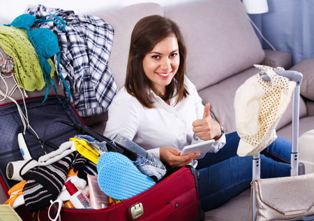 Young pleasant woman booking online for holidays at home