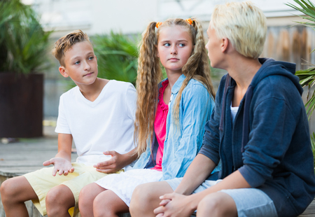 Photo pour Smiling girl with two boys having discussion outdoors - image libre de droit