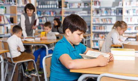 Photo pour Portrait of diligent tween boy preparing for lesson in school library, reading textbooks - image libre de droit