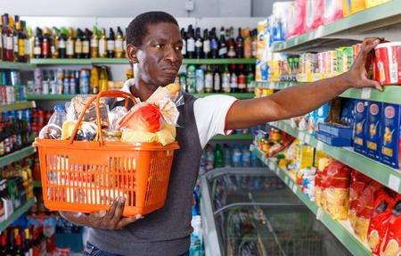 Foto für Positive glad  smiling   Afro man with shopping cart choosing goods in grocery store - Lizenzfreies Bild