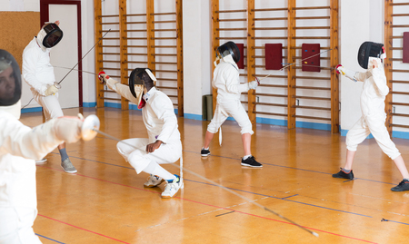 Group of kids and adults fencers with trainer engaged in fencing in gym