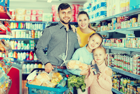 Cheerful family with two children holding full basket after shopping in food store