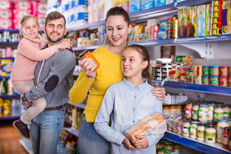 Happy parents with two daughters choosing the fresh products in a food store