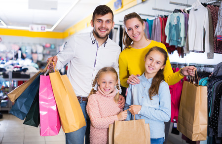 Photo pour friendly young family of four with shopping bags in clothing shop - image libre de droit