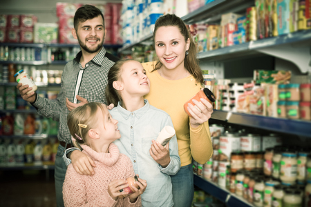 adult family of four shopping together in grocery store