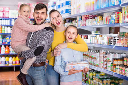 Portrait of happy smiling positive friendly family of four in supermarket