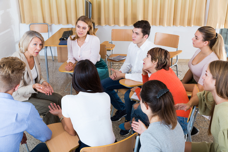 Photo pour Friendly group of young students studying in university with female tutor - image libre de droit