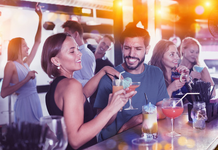 Photo pour Portrait of cheerful positive smiling females and males having fun in the bar - image libre de droit