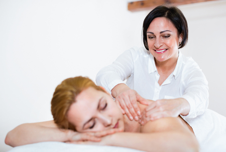 Photo pour Adult  cheerful positive masseuse makes relaxing massage shoulder zone to young woman in beauty parlor - image libre de droit