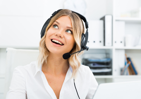 Photo pour Young girl in call center with headphones sitting with laptop - image libre de droit