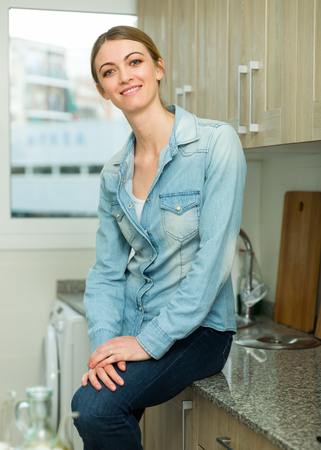 Smiling attractive girl standing at home kitchen interior, posing at camera