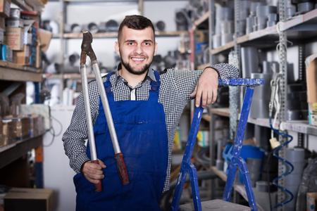 Photo pour Smiling man worker showing various instruments at workplace - image libre de droit