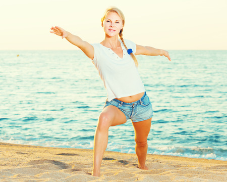 Photo pour Female 25-35 years old is doing excercises on endurance on the beach near sea. - image libre de droit