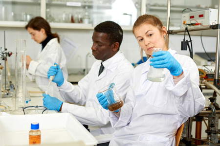 Photo pour Focused women lab technicians in glasses working with reagents and test tubes, man on background - image libre de droit