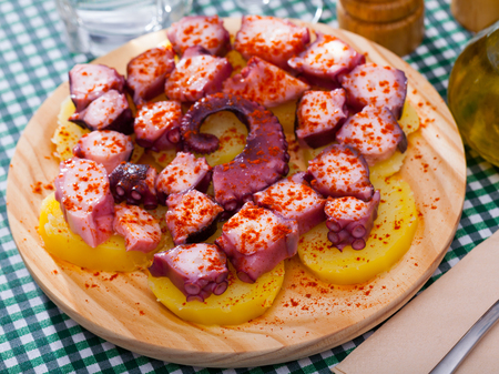 Foto de Appetizing tentacle of octopus with boiled potatoes seasoned with smoked paprika - Imagen libre de derechos