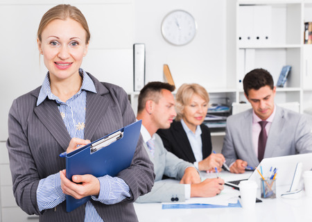 Photo pour Successful businesswoman with clipboard standing in office with colleagues behind - image libre de droit