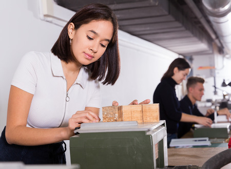 Photo pour Female student of faculty of architecture engaged in architectural modeling in university studio - image libre de droit