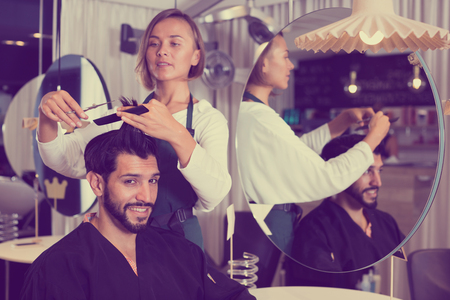 Photo pour adult hairdresser working with scissors and comb with smiling man - image libre de droit
