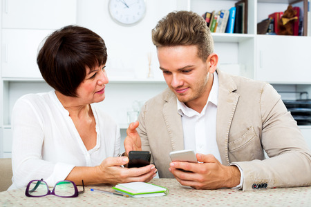 Photo pour Happy elderly mother with her young son studing new functions of smartphones - image libre de droit