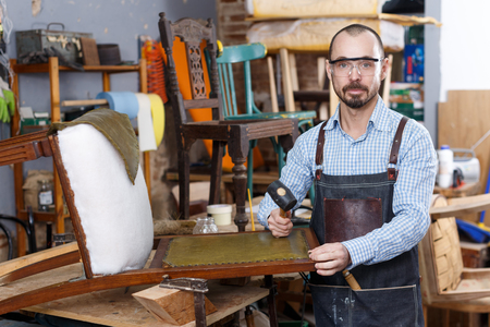 Photo pour Positive craftsman engaged in repair of vintage furniture, reupholstering chair in workshop - image libre de droit