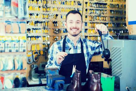 Young male worker demonstrating newly shaped key in workshop