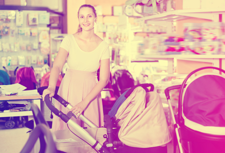 Positive  pregnant woman buying baby stroller in kids mall