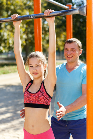 Foto de Sporty family of father and preteen girl training together outdoors, doing exercises on horizontal bar - Imagen libre de derechos