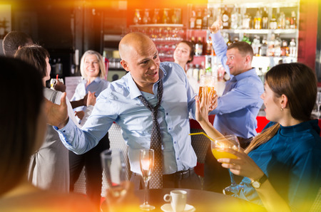 Cheerful male and female colleagues having fun on corporate party in bar