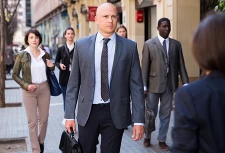 Photo pour Adult male businessman in formal wear walking down street in downtown - image libre de droit