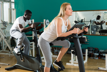 Photo pour Portrait of couple training on stationary cycles at sport club - image libre de droit
