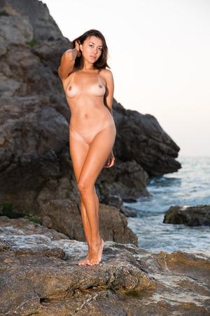 Photo pour Portrait of  sexy young nude female standing on stones at sea shore - image libre de droit