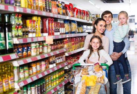 Foto für Smiling young parents with two playful little daughters buying food in hypermarket - Lizenzfreies Bild