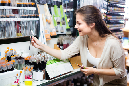 Foto für happy young brunette woman selecting brushes for painting in art department - Lizenzfreies Bild