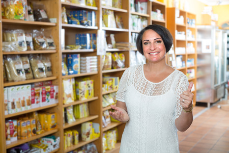 Smiling mature woman customer choosing  dietary supplements in healthy food store