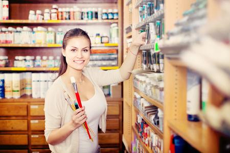 Photo pour portrait of young cheerful woman choosing paint color in tube in art shop - image libre de droit