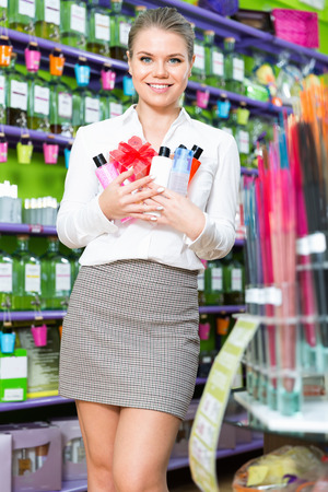 Portrait of delighted young cheerful  smiling woman with purchases in perfumery