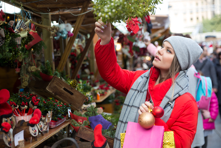 Girl shopping on street selecting decoration for home on Christmas market